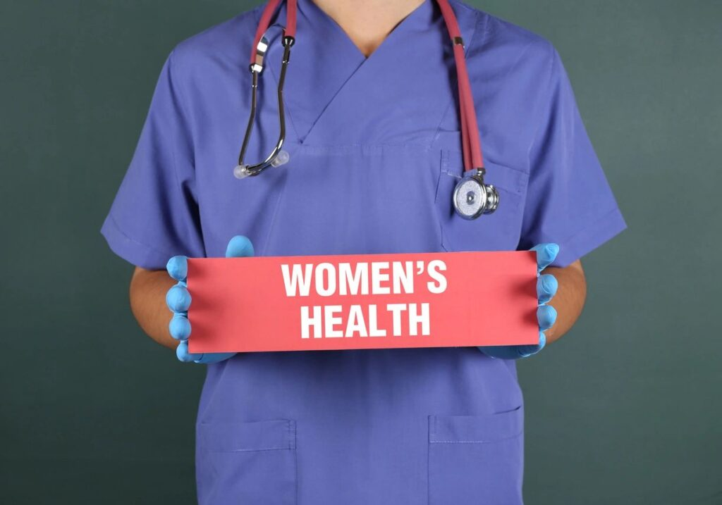 """A health staff holding a signage saying """"WOMEN'S HEALTH"""""""