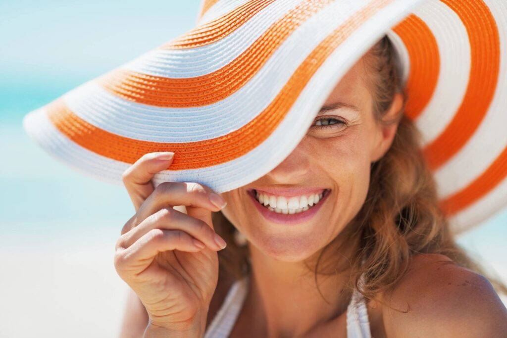A woman wearing an orange and white beach hat